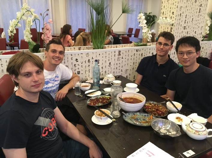 A group of people sitting at a table eating food  Description automatically generated